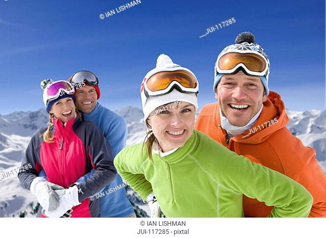 Two Couples Enjoying Winter Ski Holiday In Mountains
