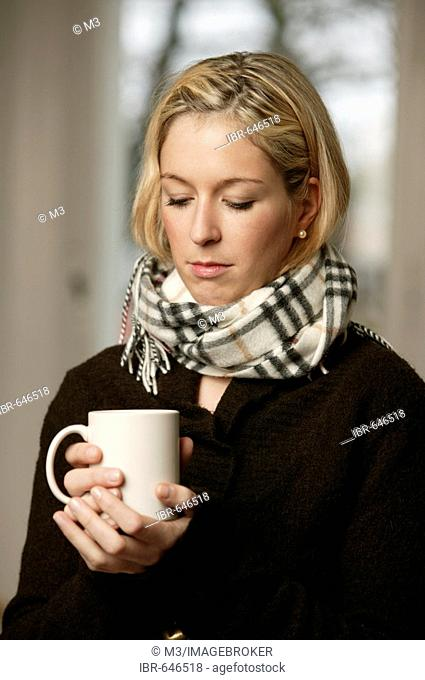 Blonde woman in dark sweater holding a mug