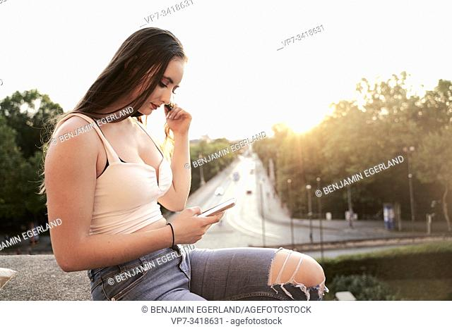 Young woman looking at smartphone. Munich, Germany