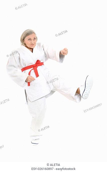 Senior woman in karate pose on white background