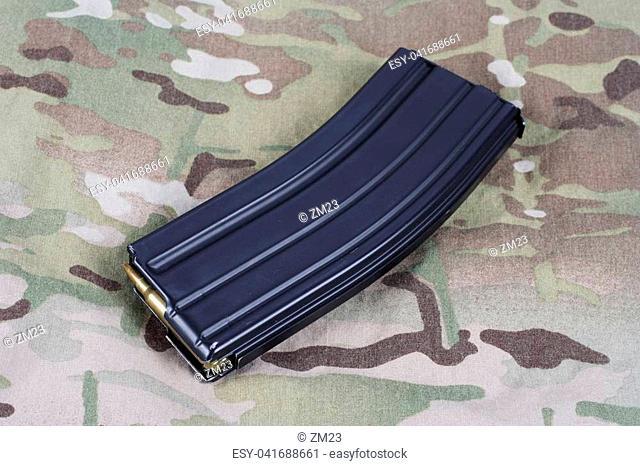 M-16 magazine with cartridges on camouflage uniform background