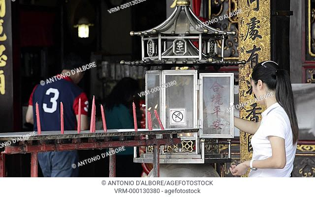 A chinese woman lighting up candle in the Cheng Hoon Teng Temple. Malacca. Malaysia