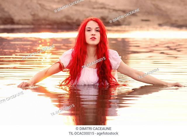 Young woman with long red hair wearing white dress standing in lake facing camera