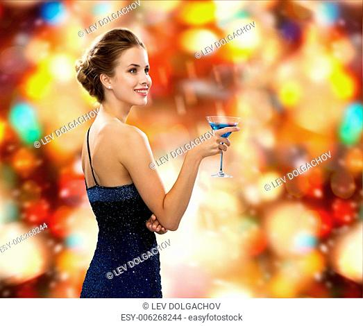 party, drinks, winter holidays, luxury and celebration concept - smiling woman in evening dress holding cocktail over red christmas lights background