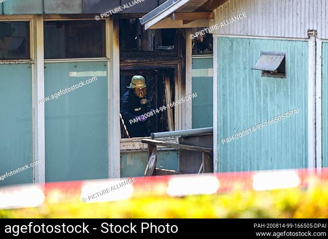 14 August 2020, Hamburg: A fire investigator wearing a breathing mask is standing in the burnt out storeroom of a well-known restaurant of a sailing club on...