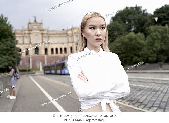portrait of Asian woman with arms crossed, serious looking, in front of Landtag of Bavarian, Bavarian Parliament, in Munich, German