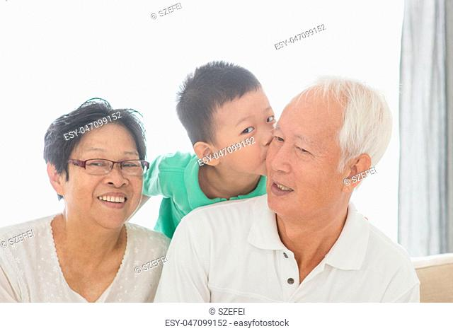 Grandchild kissing grandparents