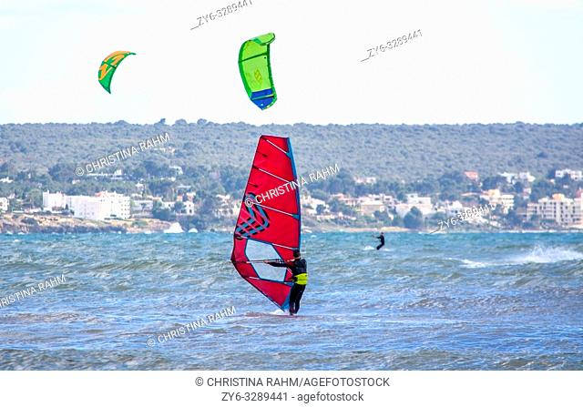 CAN PASTILLA, MALLORCA, SPAIN - APRIL 6, 2019: Windsurfer with red sail plays in the green waves on a windy and sunny day on April 6, 2019 in Can Pastilla