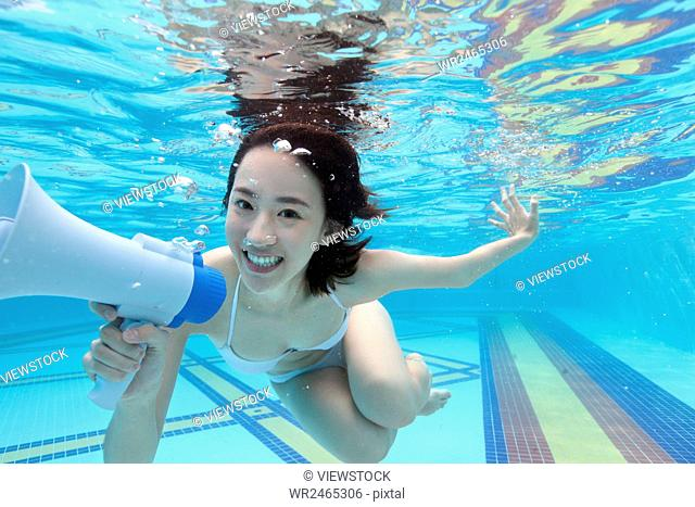 Underwater young woman holding a megaphone