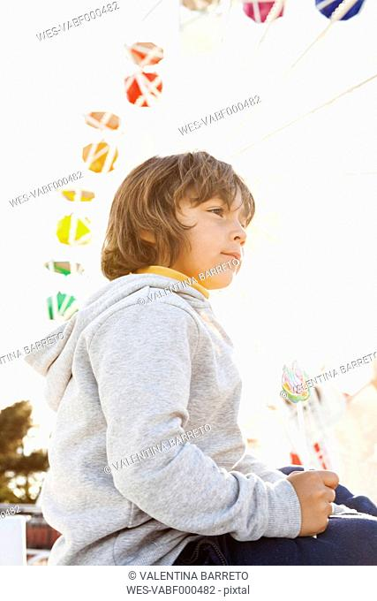 Little boy with lollipop sitting in front of big wheel