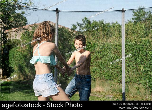 Horizontal photo of a blonde boy and a brunette girl holding hands playing on a trampoline on a green playground. The teenager and the child wear short jeans...