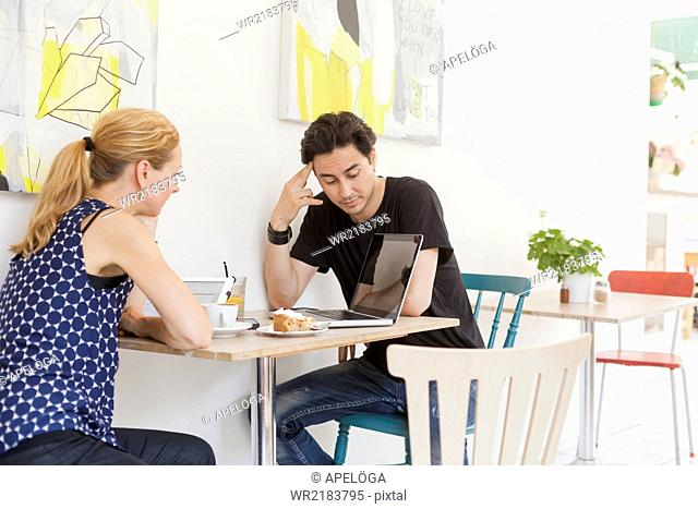Man and woman using laptop at cafe table