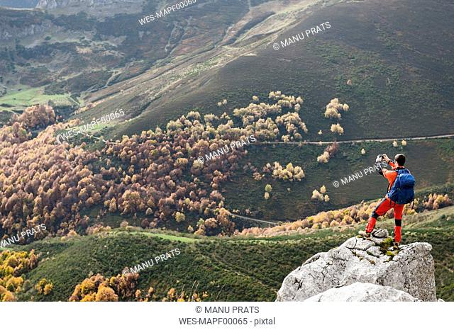 Spain, Picos de Europa, mountaineer on rock taking a picture