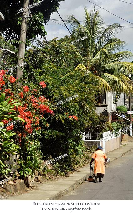 Mauritius, a woman cleaning a street in the inner part of the island