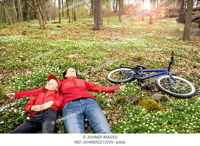 Mother with son resting in forest