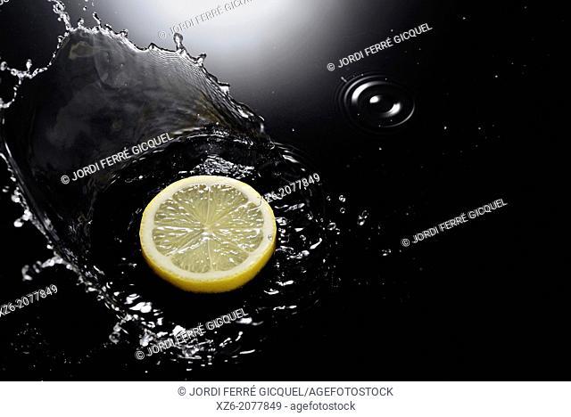 A lemon slice splashing in water on black background