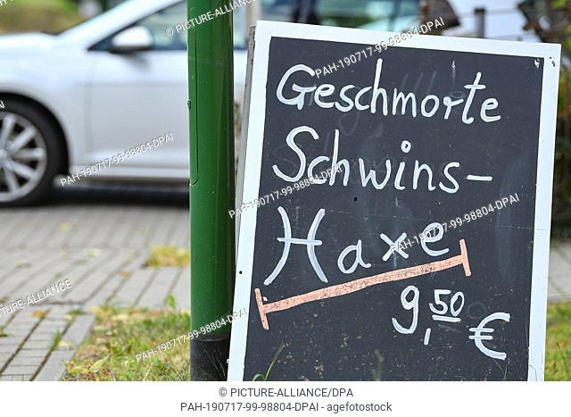 "17 July 2019, Brandenburg, Tiefensee: The lunch dish """"Geschmorte Schwins-Haxe 9,50 ·"""" is placed on a display in front of a restaurant"