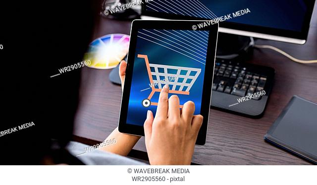 Hand touching shopping cart icon on tablet PC