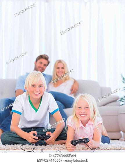 Children on the carpet playing video games in the living room