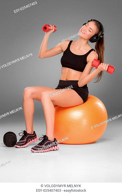 Sporty woman doing aerobic exercise with red dumbbells on a fitness ball on grey background