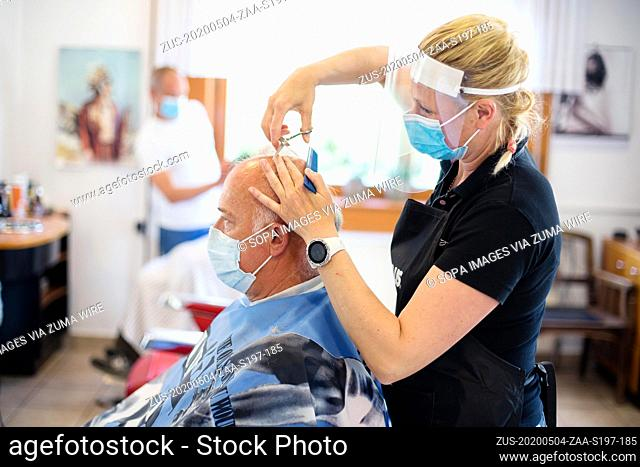 May 4, 2020, Kranj, Slovenia: A hairdresser wearing a face mask and shield as preventive measure cuts hair of a client amid coronavirus crisis