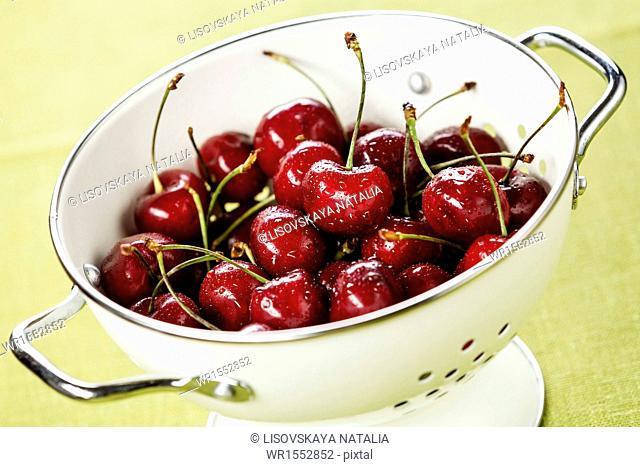 Wet ripe cherries in white colander