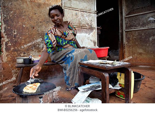 woman is baking a bread called Chapati made of mais flour on a charcole oven in front of a simple house, Uganda, Jinja