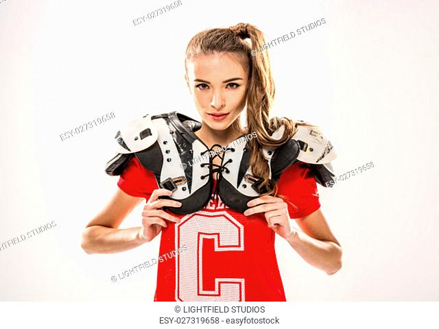 Female football player looking at camera on grey