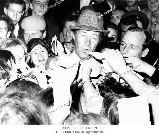 British Actor Rex Harrison stepped into a swarm of Russian autograph seekers outside his hotel. Harrison was in Moscow for a film Festival