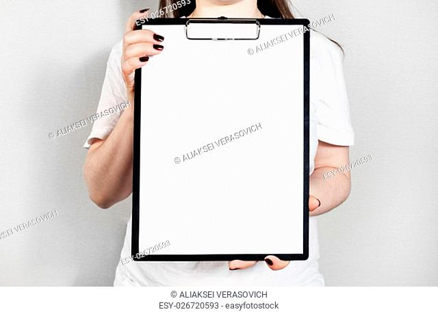 Woman holding clipboard with a blank sheet of paper. Blank paper poster in female hands. Blank template for graphic designers portfolios