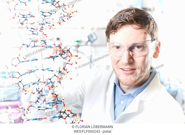 Germany, Portrait of young scientist with DNA model, smiling
