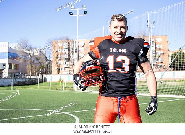 Portrait of smiling American football player holding helmet