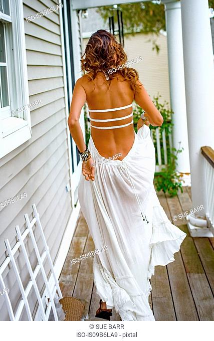 Rear view of woman in long white dress leaving house porch