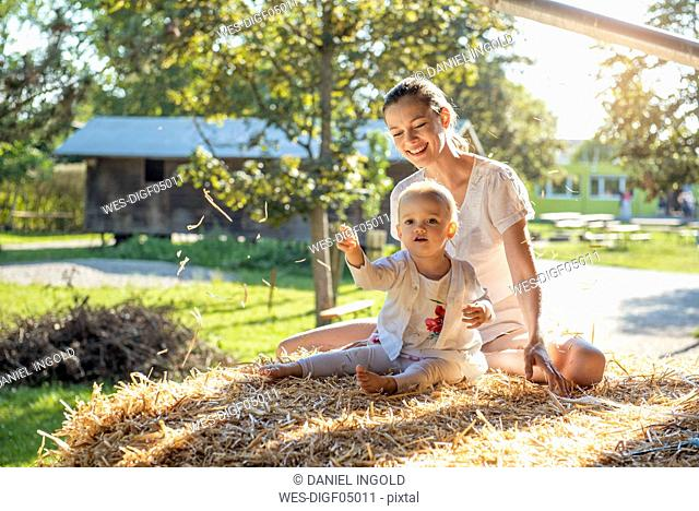 Happy mother and little daughter playing with straw on a farm