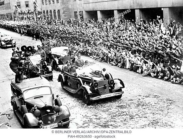 People cheer at Hitler's victory procession outside of the new Reichs Ministry of Aviation on Wilhelmplatz in front of a crowd of cheering people as Hitler...