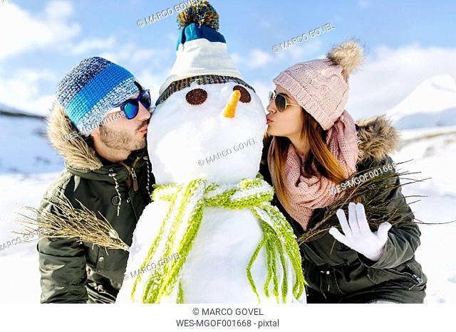 Spain, Asturias, couple kissing a snowman