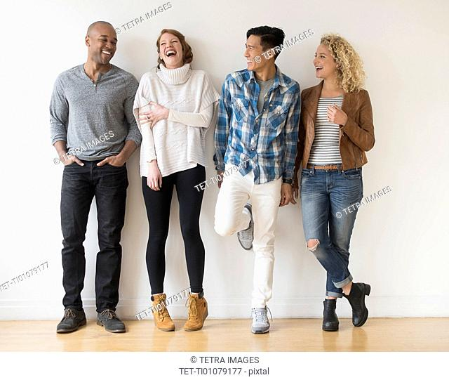 Laughing friends standing against white wall