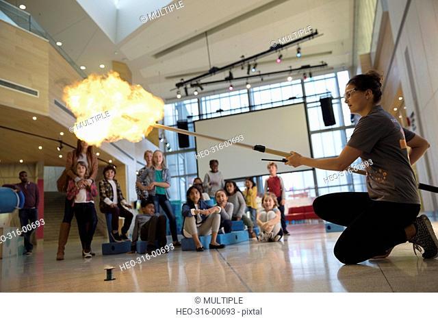 Children watching scientist conducting fire demonstration in science center