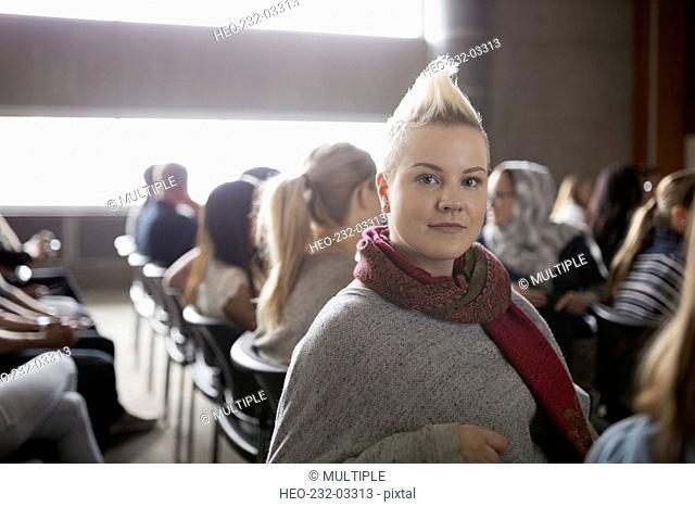 Portrait confident woman with blonde mohawk auditorium audience