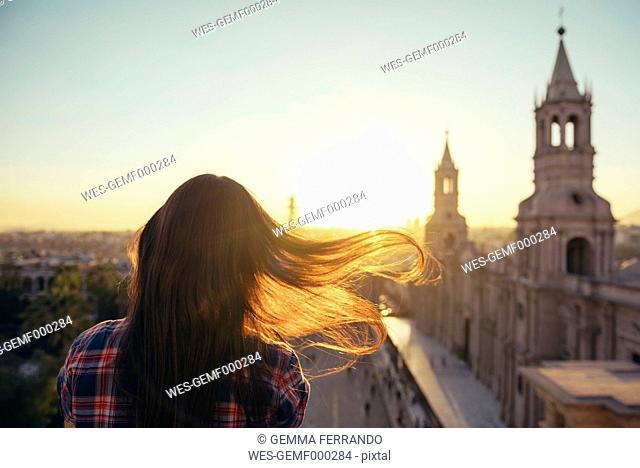 Peru, Arequipa, woman looking at Plaza de Armas enjoying sunset