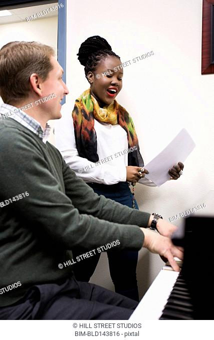 Vocal teacher and student singing at piano