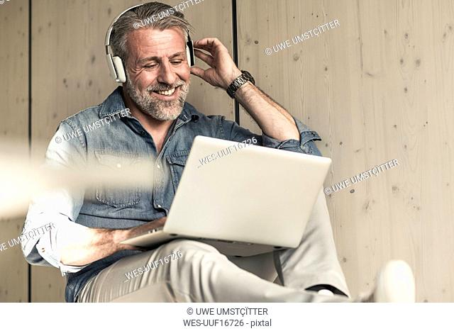 Casual mature businessman sitting down with laptop and headphones