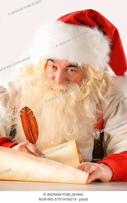 Real Santa Claus writing list of gifts or responding to children's letters on old paper scroll, isolated on white background