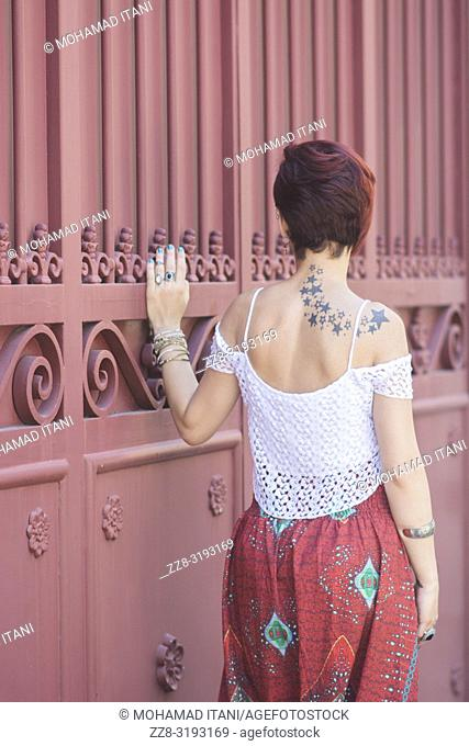 Rear view of a tatooed young woman with short red hair hand touching the gate