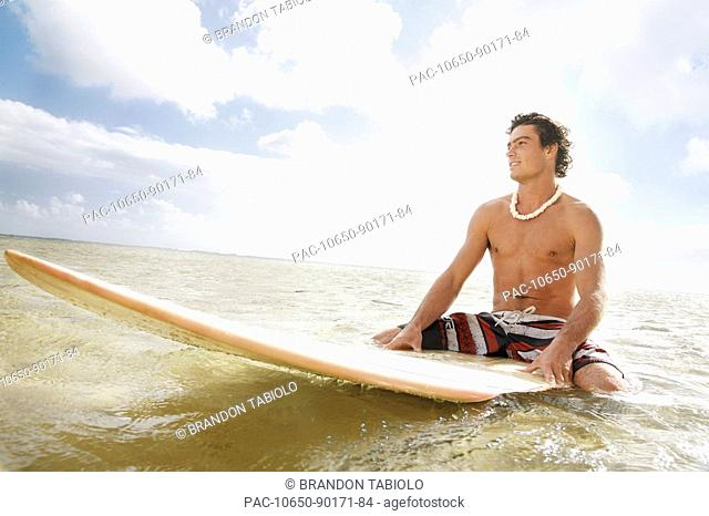 Hawaii, Oahu, Young man sitting on his surfboard at the shoreline