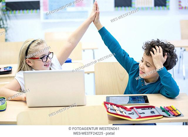 Schoolboy and schoolgirl with laptop high fiving in class