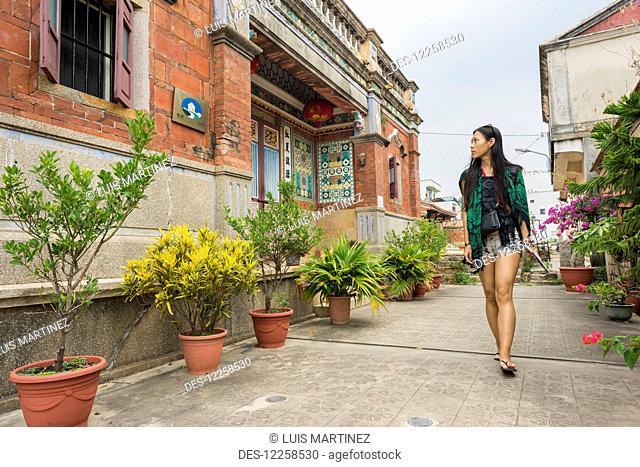 A young woman walks down a walkway and looks at buildings; Shuitou, Kinmen Island, Taiwan