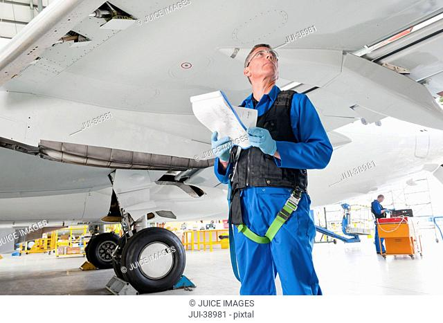 Engineer with paperwork below wing of passenger jet in hangar