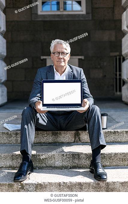 Portrait of senior businessman sitting on stairs showing laptop