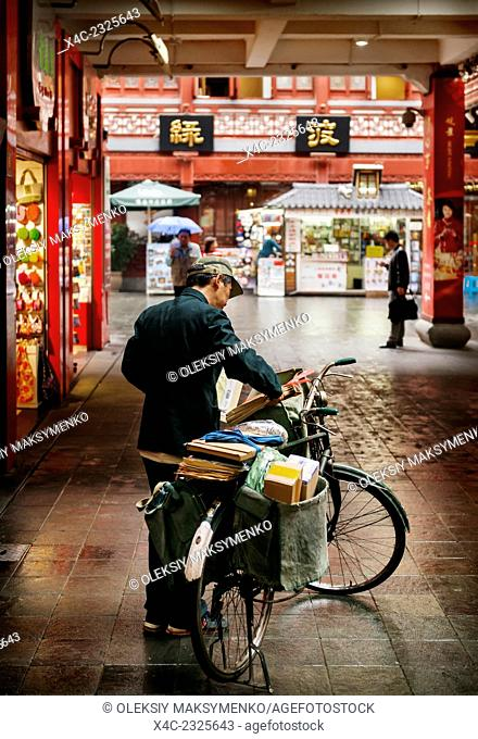 Postman delivering mail by bike in the Old city of Shanghai, China 2014
